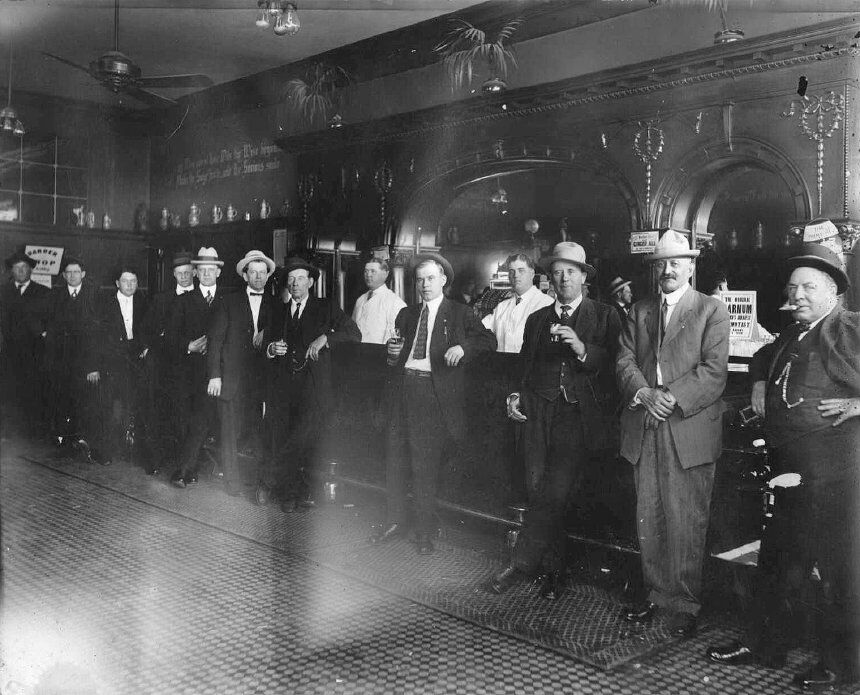 "The Mint Saloon. Owner was J. W. Buckley. Sign at left says ""Barber Shop in Lobby."" At the right are two signs: ""Puritan Club Pale Ginger Ale"" ""The Original [B?]arnum [Amer?]ica's Greatest [Hyp?]notist, [?] Laughs, [?] & Tears"""