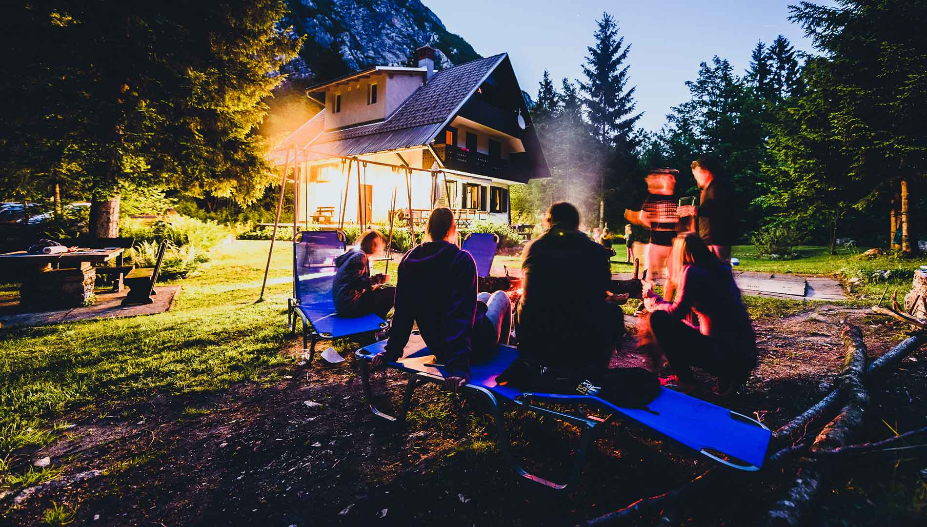 people sitting around camp fire outside montana house