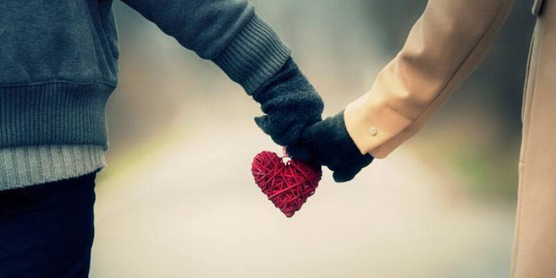 Unconditional love with a couple holding hands with a heart
